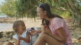 De familie zit op een tropisch strand en eet vruchten in langzame motie stock videobeelden