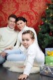 De familie zit thuis op vloer met giften dichtbij Kerstboom Royalty-vrije Stock Foto's