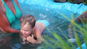 De familie zwemt in een klein meer op een hete de zomerdag De oma leert om een klein kind te zwemmen Tuin, bloemen en installatie stock video