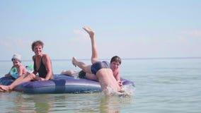 De familie zwemt in het overzees op een grote opblaasbare matras Gelukkige kinderjaren positief stock footage