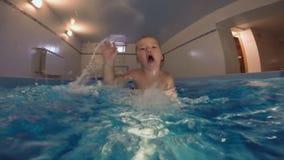 De familie zwemt in de pool Een kleine zoon met zijn vader geniet gelukkig van badend stock videobeelden