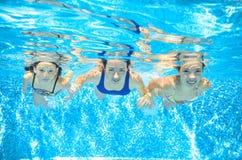De familie zwemt in pool onderwater, hebben de moeder en de kinderen pret in water, Royalty-vrije Stock Foto's