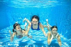 De familie zwemt in pool onderwater, hebben de moeder en de kinderen pret in water, Stock Foto's