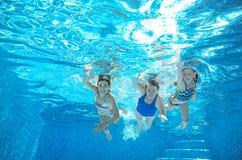De familie zwemt in pool of overzees onderwater, hebben de moeder en de kinderen pret in water Stock Afbeeldingen