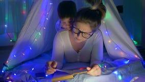 De familieatmosfeer, gevende moeder leest sprookjes die aan jong geitje in tipi met slingers bij ruimte liggen stock footage