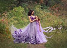 De familiefoto van mamma en dochter in luxueuze purpere fladderende kleding met bloemen, bevindt zich in het de zomerbos royalty-vrije stock foto's
