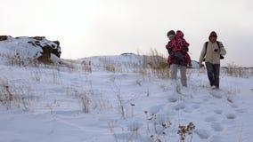De familiegangen langs de snow-covered heuvel, een blizzard begint stock video