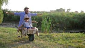 De familieidylle, kindjongen heeft pret met zijn vader veronderstellen dat zij als een vliegtuig in kruiwagen bij platteland vlie stock videobeelden