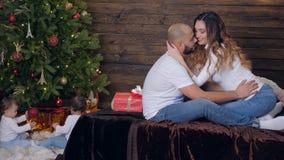 De familieidylle, paar kust zacht op bed in vooravond van nieuw jaar op kinderen die als achtergrond onder Kerstboom zitten stock video