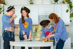 De familiekoks samen Echtgenoot, vrouw en hun kinderen in de keuken De familie kneedt deeg met bloem royalty-vrije stock afbeelding