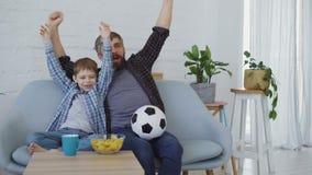 De de familieledenvader en zoon letten voetbal op gelijke op TV thuis, het toejuichen, het vieren overwinning en het eten van sna stock video