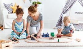 De de familiemoeder en kinderen spelen een stuk speelgoed spoorweg in speelkamer royalty-vrije stock afbeelding