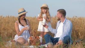 De familiepicknick op korrelgebied, weinig jong geitjemeisje giet melk in de glazen van haar jonge vrolijke ouders tijdens het he stock videobeelden