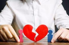 De familiepsycholoog verzamelt het rode hart dichtbij een paarminnaars Vernieuwing van de verhouding Familiepsychotherapist de di royalty-vrije stock foto