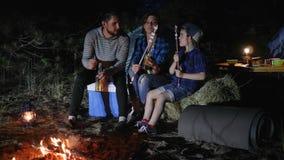 De familiereis op weekend in bos, reiskamp van Amerikaanse familie in bos, ouders drinkt bier en het kind eet zefier stock video