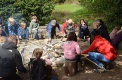 De families rond een kampvuur maken broden op stokken stock fotografie
