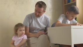 De familietijd van de vader - lezing voor dochter, die zoon helpen stock footage