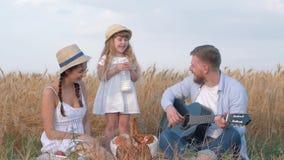 De familievakantie in gebied, de jonge gitaar van het vaderspel en lach met zijn vrouw bij dochter drinkt en likt melkbakkebaarde stock footage