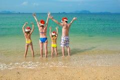 De familievakantie op Kerstmis en Nieuwjaarvakantie, de gelukkige ouders en de kinderen in santahoeden hebben pret op strand Royalty-vrije Stock Foto's