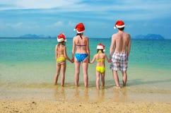 De familievakantie op Kerstmis en Nieuwjaarvakantie, de gelukkige ouders en de kinderen in santahoeden hebben pret op strand Stock Afbeeldingen