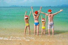 De familievakantie op Kerstmis en Nieuwjaarvakantie, de gelukkige ouders en de kinderen in santahoeden hebben pret op strand Royalty-vrije Stock Foto