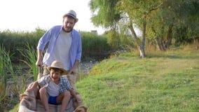 De familievakantie in openlucht, vrolijke papa draagt blij jong geitje in een kruiwagen op aard in langzame motie stock footage