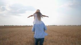 De familieverhouding, vrolijke jonge papalooppas met dochter op zijn schouders die haar schudt dient gouden korrel in stock footage