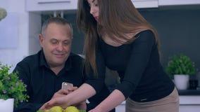 De familievrije tijd, gelukkig meisje geeft traktaties voor zijn vader tijdens ontbijt in keuken stock footage