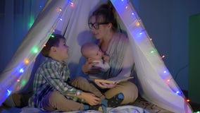 De familievrije tijd, mamma leest sprookjes aan haar twee zonen die in de wigwam in avond zitten stock videobeelden