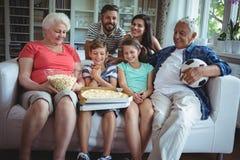 De familiezitting van meerdere generaties met popcorn en pizza terwijl het letten van voetbal op gelijke Royalty-vrije Stock Fotografie
