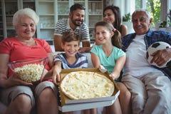 De familiezitting van meerdere generaties met popcorn en pizza terwijl het letten van voetbal op gelijke Stock Afbeelding