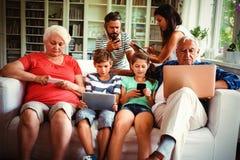 De familiezitting van meerdere generaties op bank en het gebruiken van diverse technologieën royalty-vrije stock foto