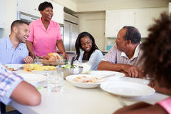 De Familiezitting van meerdere generaties rond Lijst die Maaltijd eten stock afbeeldingen