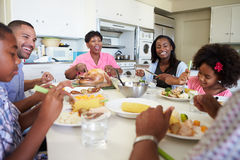 De Familiezitting van meerdere generaties rond Lijst die Maaltijd eten stock foto's