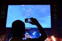 De fans genieten van overleg in ventilatorstreek van zaal tijdens overleg menigte van mensensilhouetten met hun omhoog handen royalty-vrije stock fotografie