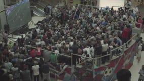 De fans letten op de levende uitzending van de gelijke Rusland-Uruguay in de wandelgalerijgalerij stock footage
