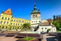 De fantastische klokketorenbouw in de beste toeristische stad, rustende plaats met banken, Sighisoara, Transsylvanië, Roemenië, E stock foto's