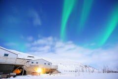 De fantastiska nordliga ljusen över det vidsträckta fältet i vintern Island royaltyfri bild