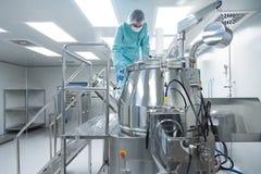 De farmaceutische arbeider van de fabrieksmens in beschermende kleding stelt productielijn in steriele arbeidsvoorwaarden in werk stock afbeeldingen