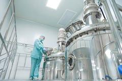 De farmaceutische arbeider van de fabrieksvrouw in beschermende kledings werkende productielijn in steriel milieu stock afbeeldingen