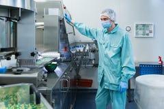 De farmaceutische arbeider van de de industriemens in beschermende kledings werkende productie van tabletten in steriele arbeidsv royalty-vrije stock afbeeldingen