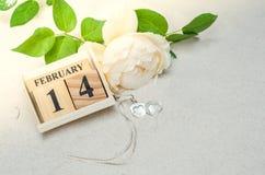 14 de febrero, calendario de madera con el medallón de la forma del corazón y flor Fotos de archivo libres de regalías
