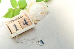 14 de febrero, calendario de madera con el medallón de la forma del corazón y flor Imagen de archivo libre de regalías