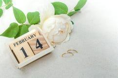 14 de febrero, calendario de madera con los anillos y flor en backg de la arena Imágenes de archivo libres de regalías