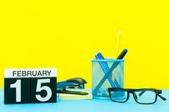 15 de febrero Día 15 del mes de febrero, calendario en fondo amarillo con los materiales de oficina Flor en la nieve Foto de archivo