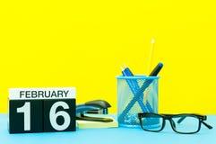 16 de febrero Día 16 del mes de febrero, calendario en fondo amarillo con los materiales de oficina Flor en la nieve Fotografía de archivo