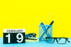 19 de febrero Día 19 del mes de febrero, calendario en fondo amarillo con los materiales de oficina Flor en la nieve Imagen de archivo libre de regalías