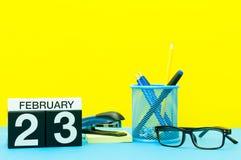23 de febrero Día 23 del mes de febrero, calendario en fondo amarillo con los materiales de oficina Flor en la nieve Fotos de archivo