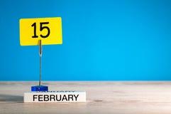 15 de febrero Día 15 del mes de febrero, calendario en poca etiqueta en el fondo azul Flor en la nieve Espacio vacío para el text Imagen de archivo