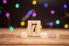 7 de febrero Día 7 de sistema del mes de febrero en calendario de madera en el centro del fondo oscuro con el bokeh de la guirnal imagen de archivo